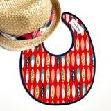 Little Dragon by Lauren Unlimited red and navy blue surf board laminated cotton baby bib teamed with a straw fedora hat