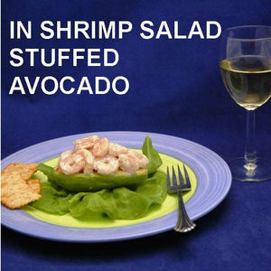 Half avocado on bib lettuce, stuffed with Ginger Sesame Shrimp Salad, served with white wine