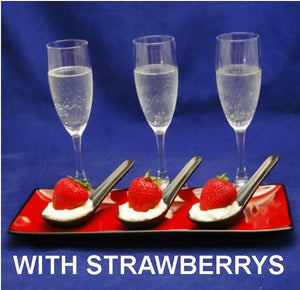 Strawberries nestled in a bed of White Chocolate Amaretto Mousse in black tasting spoons, served with champagne
