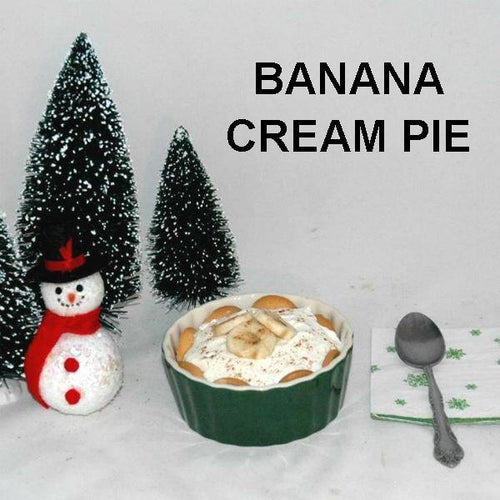 White Chocolate Banana Cream Pie with vanilla wafer crust in individual ramekin, garnished with banana slices and cinnamon Christmas