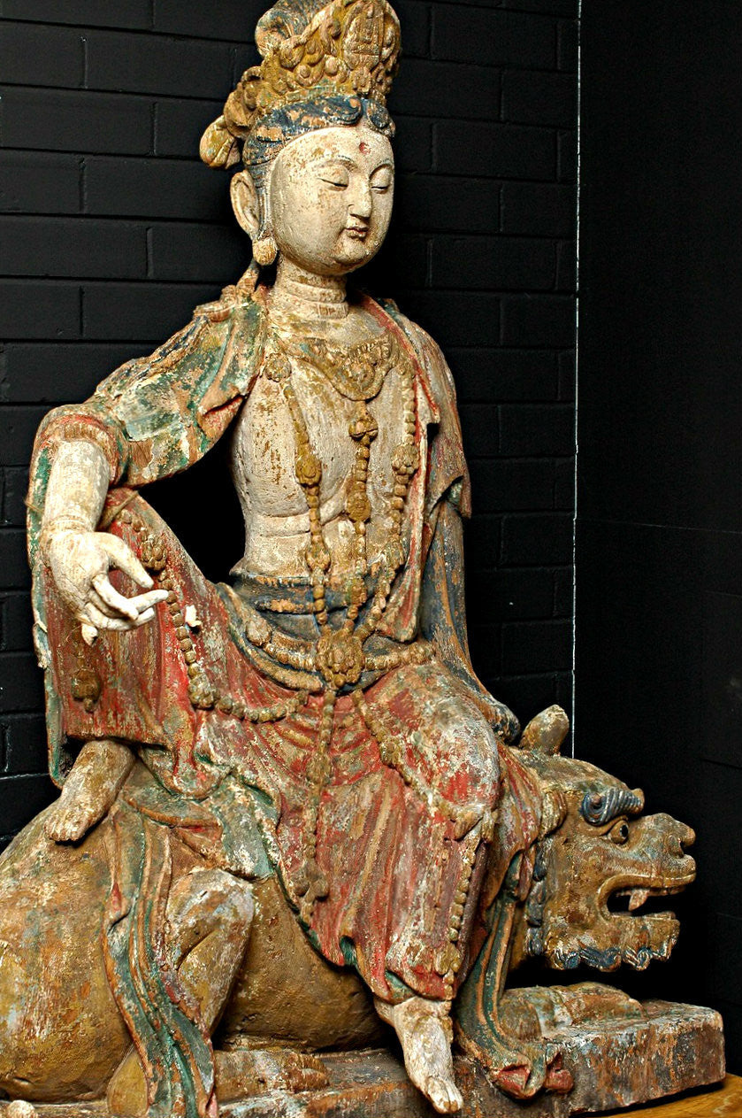 A Carved Wooden Figure of Guanyin Riding a Lion, Late Ming/early Qing period