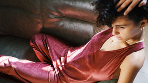 THE B.O.D Corduroy Jumpsuit Bordeaux, model wearing jumpsuit lounging on sofa