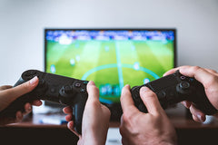 Image of a 2 pairs of hands holding games controllers, playing a video game