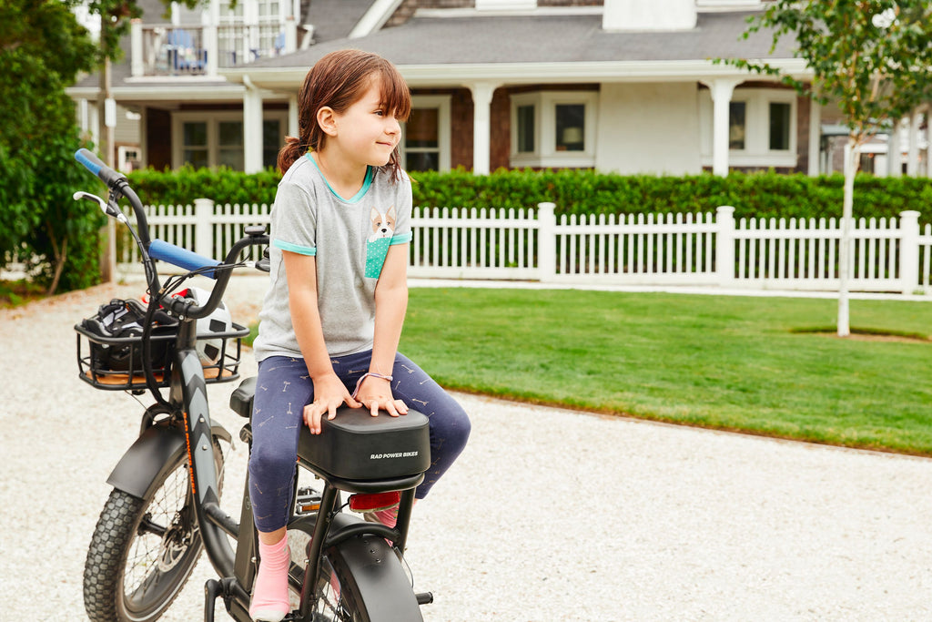 Accessorized RadRunner electric bike with little girl sitting on passenger seat