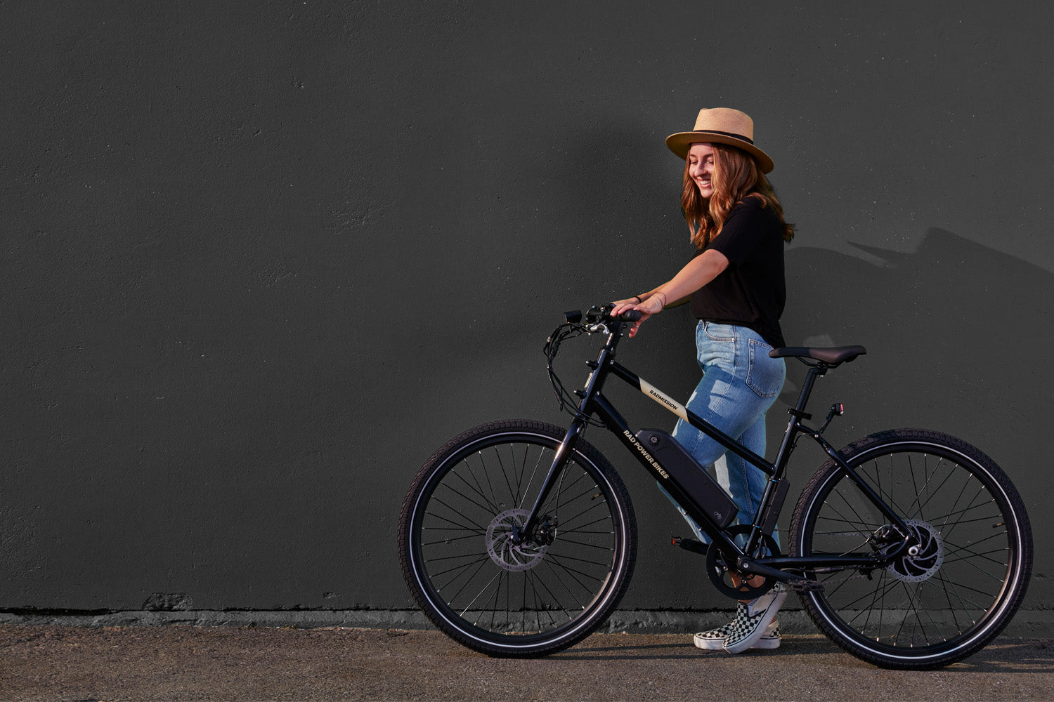 woman standing with black bike