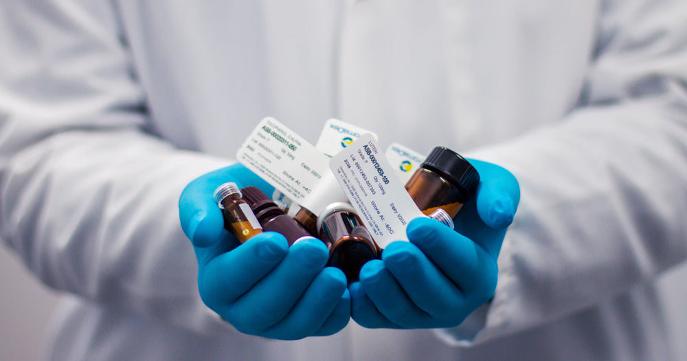 Doctor with handful of prescription medicines