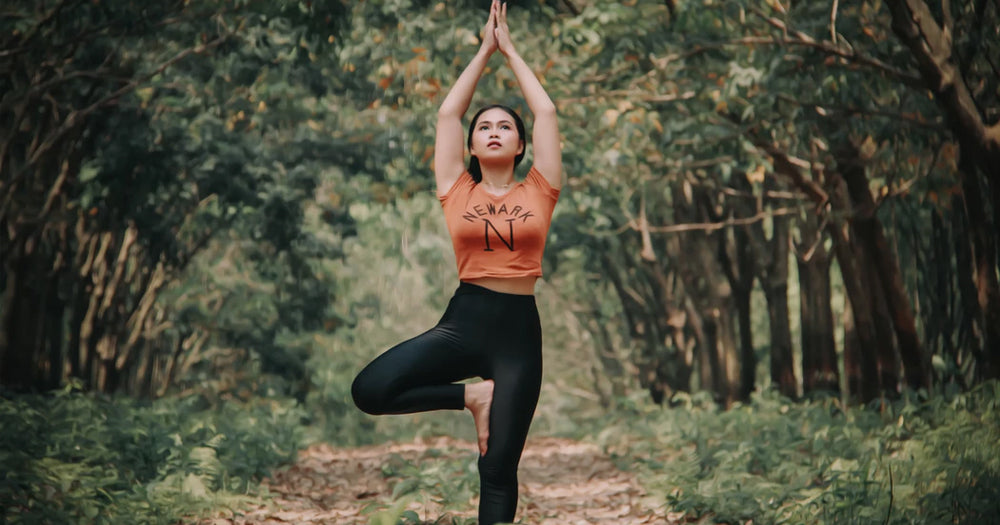Woman doing yoga in a tree orchard