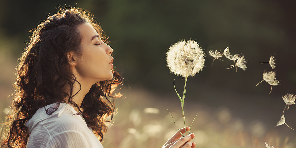 woman making wishes by blowing on a dandelion