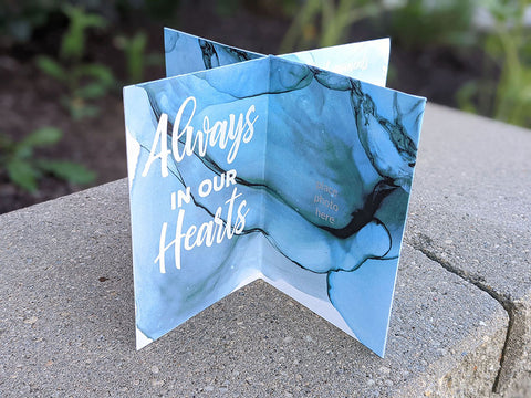 """8 panel paper table centerpiece with the theme """"always in our hearts"""" for a celebration of life event. The other panels have fill in the blank prompts for remembering your loved one. Waves theme of blues and greens dye ink."""