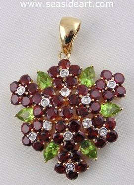 A Ladie's 14kt Yellow Gold Pendant with diamond, white sapphire, garnet and peridot.