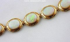 A gorgeous vintage (1960s) 14K yellow gold bracelet set with twelve natural solid oval cabochon opals.