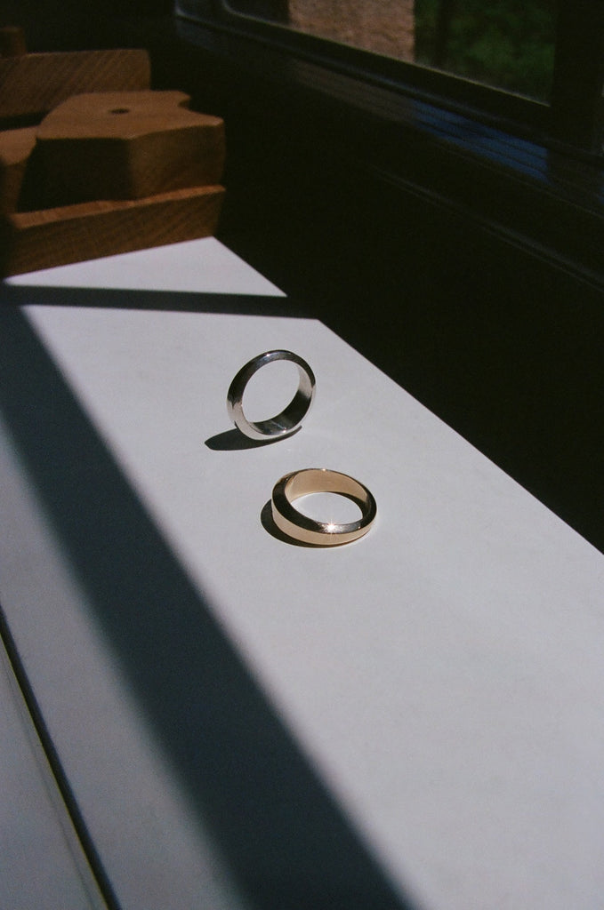Two Abel Facet Rings, one in sterling silver and one in 14 karat yellow gold, lay in the sun.