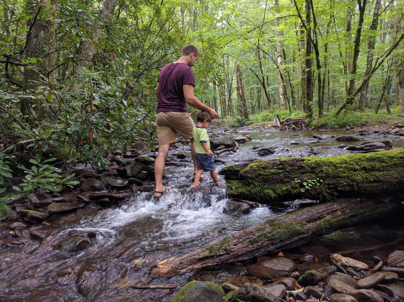 man and child walking through a mountain stream