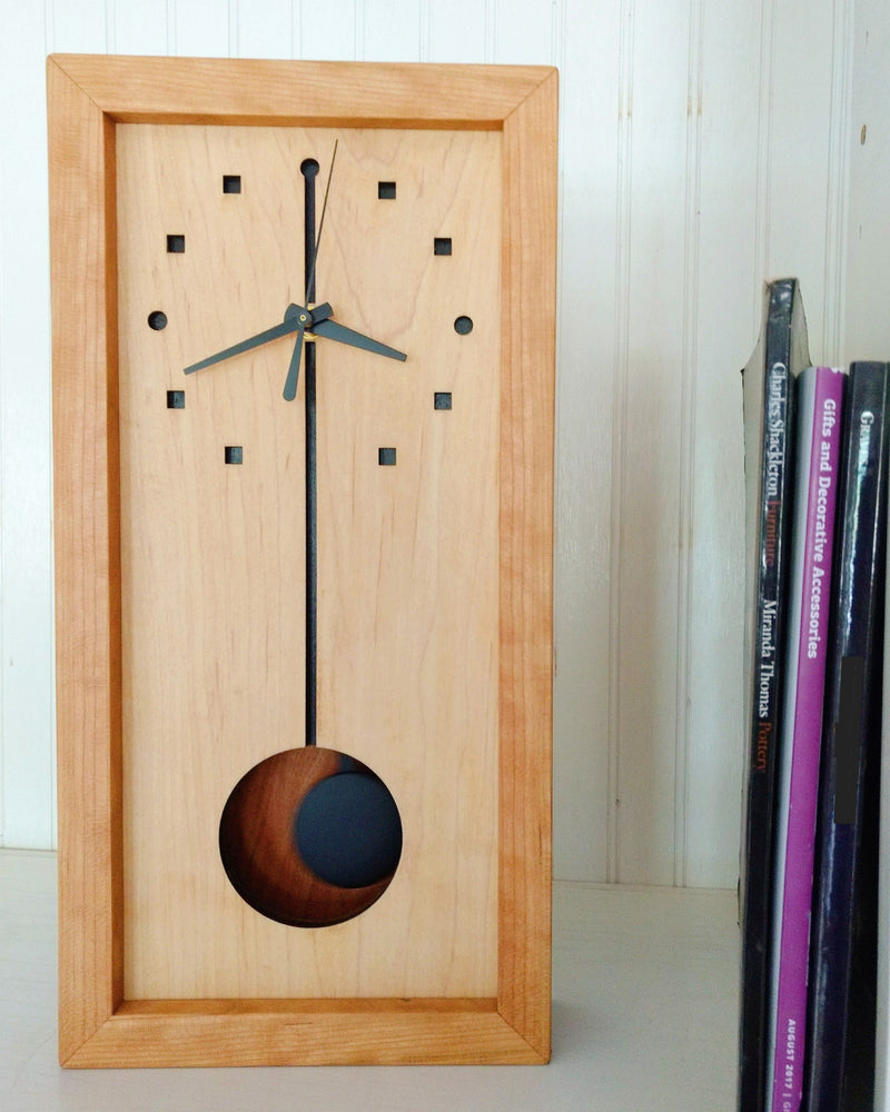 Vertical rectangular cherry wood clock with black pendulum on white shelf with books.