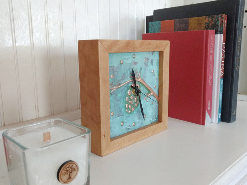 Square clock framed with cherry wood and patina copper face with pine cone design on a bookshelf.