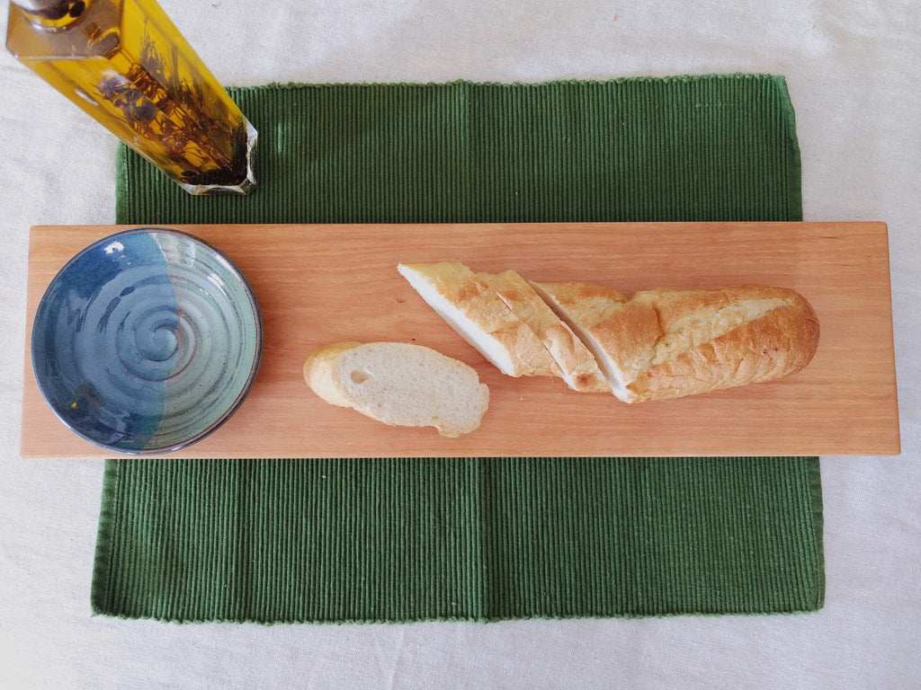 Rectangular cherry wood board with blue and green dipping bowl on green placemat with bread and oil.