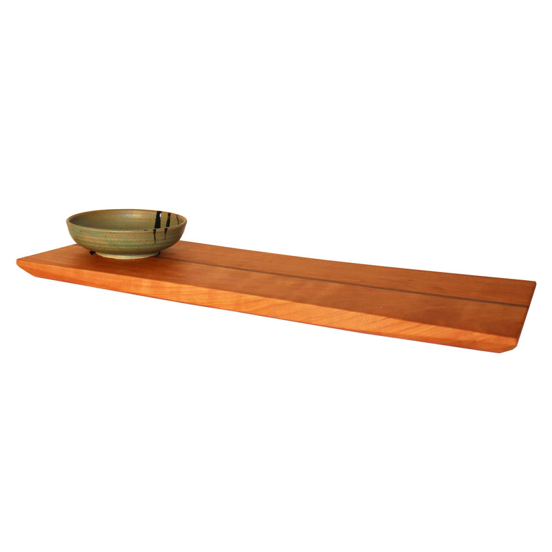 Curved edge rectangular cherry wood serving board with green dipping bowl.