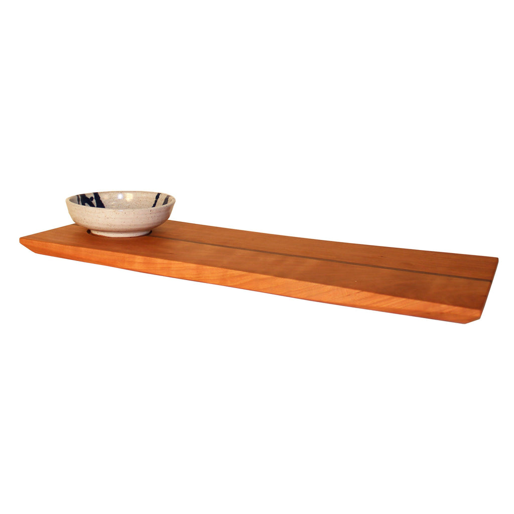 Curved edge rectangular cherry wood serving board with white and blue dipping bowl.