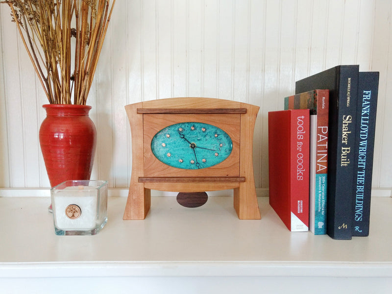 Cherry wood clock with two tapered legs, patina copper face, walnut pendulum on white bookshelf.
