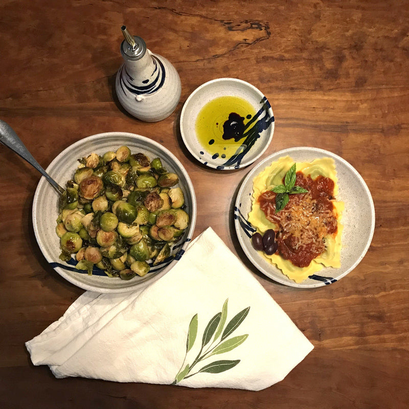 White and cobalt blue bowls collection on table, with pasta, Brussels sprouts, olive oil and herbs.