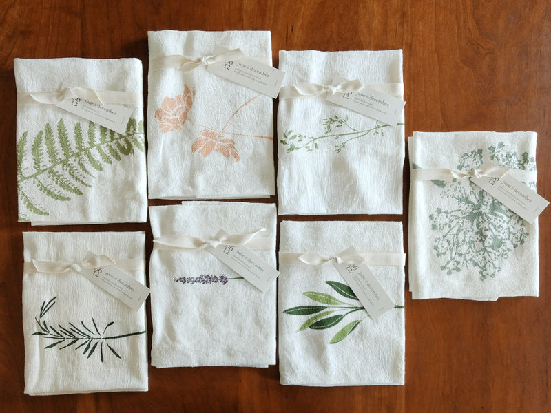 Group of seven white flour sack cotton towels with various herbal and floral screen printed graphics