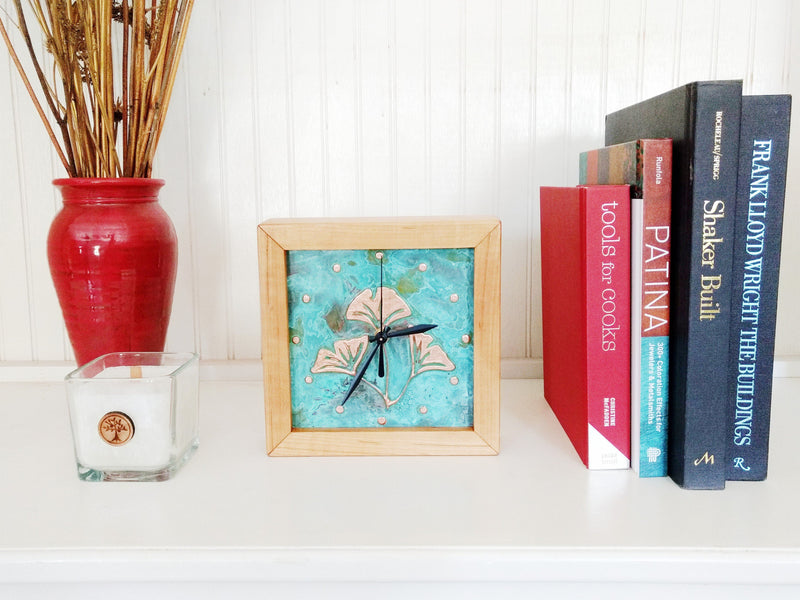 Square Clock framed with cherry wood and patina copper face with ginkgo design on a shelf with books
