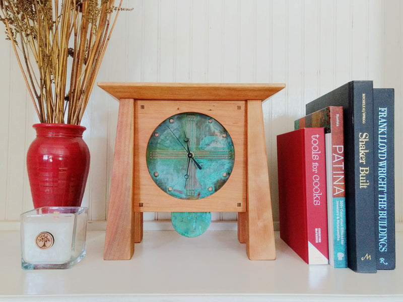 Cherry wood clock, 4 tapered legs, patina copper face & pendulum on white shelf with books & vase.