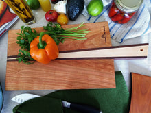 Tapered rectangular cherry wood cutting board with walnut and maple handle sliced in middle of board