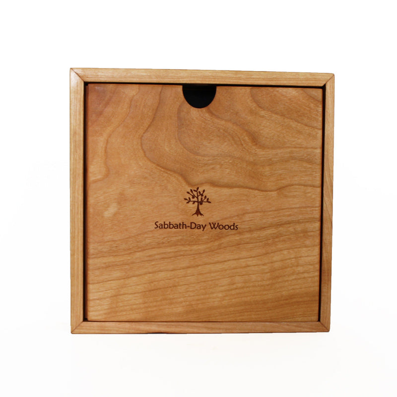 Back view: square cherry wood clock with centered imprint of Sabbath-Day Woods logo.