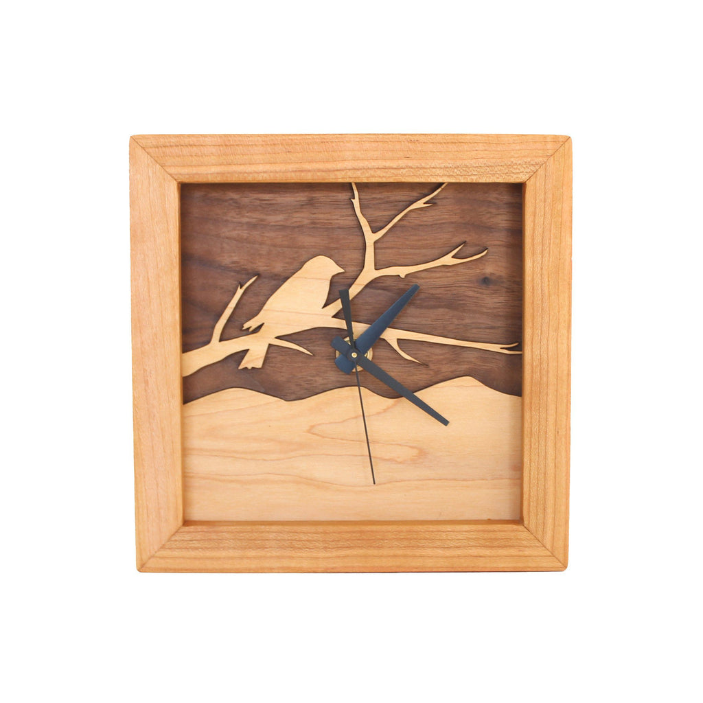 Square clock framed with cherry wood and a walnut and maple face of bird on a branch design.