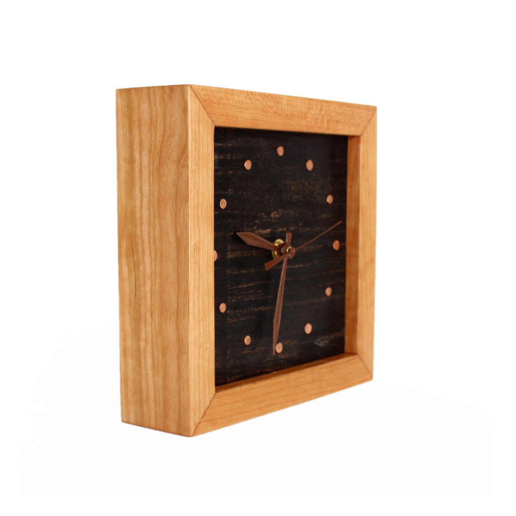 Side view: square cherry wood clock frame with painted black face with copper tack time markers.