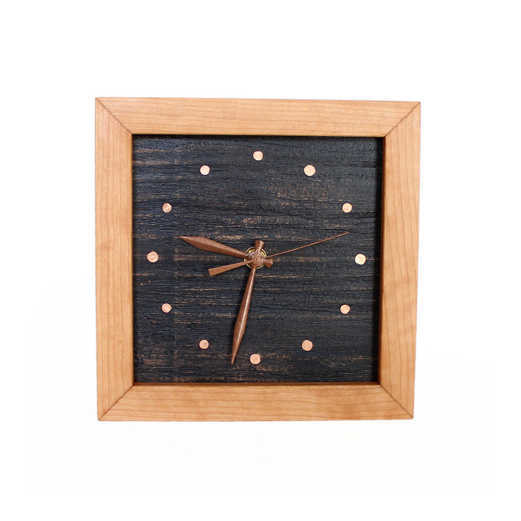 Square clock framed with cherry wood and painted black wood face with copper tack time markers.