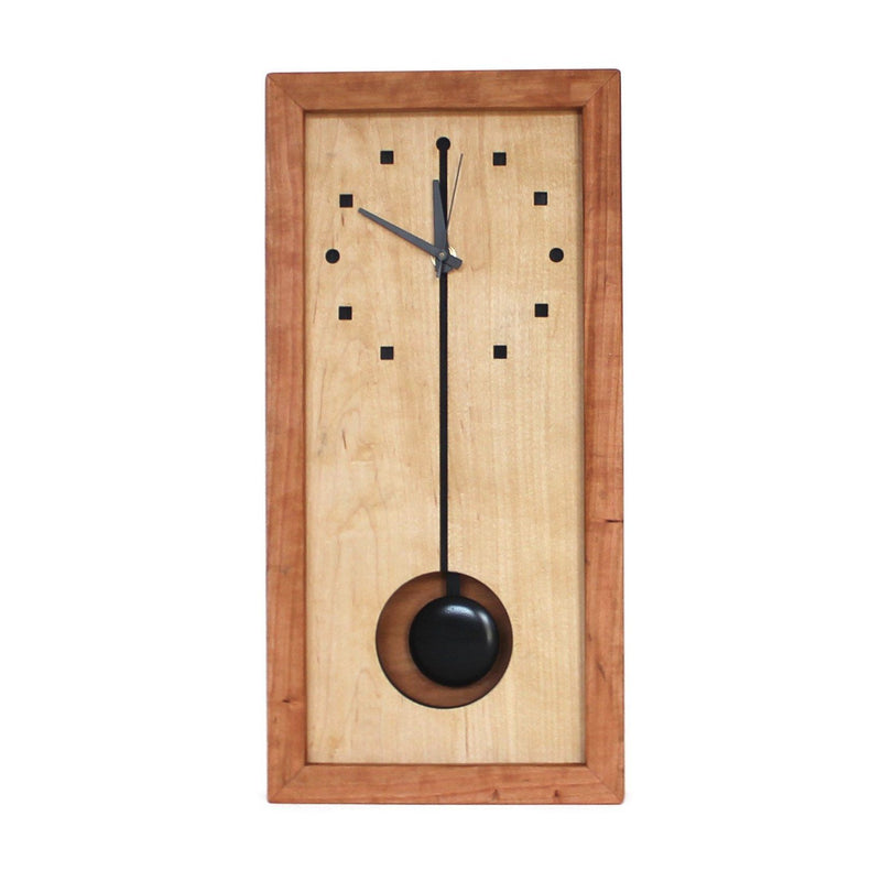 Vertical rectangular cherry wood clock with black pendulum and black time markers.