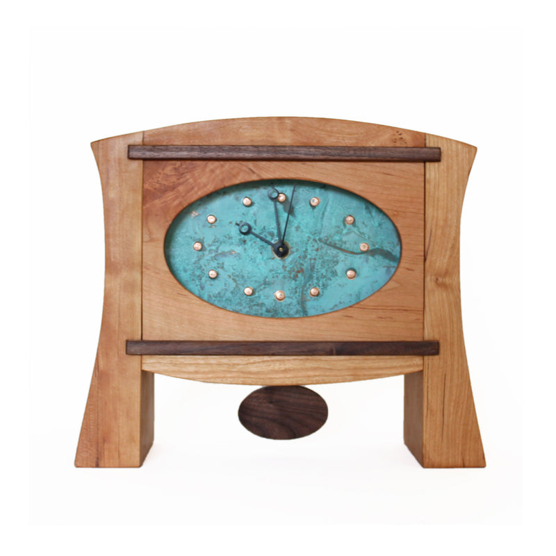 Thick cherry wood mantel clock with two tapered legs, patina copper face, walnut pendulum.