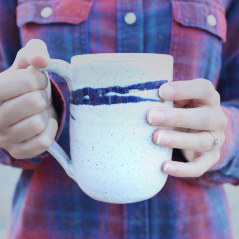 Woman in flannel holding with both hands white mug with cobalt blue accent lines.