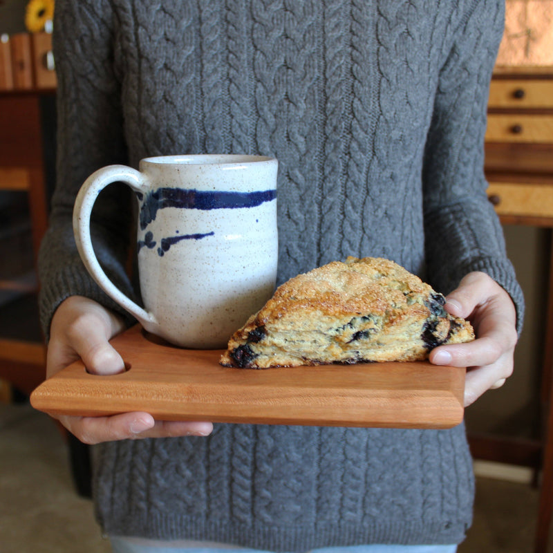 Woman holding cherry wood pastry board with pastry and white and cobalt blue mug on it.
