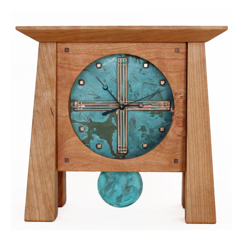 Best-selling cherry wood grand mantel clock with striking patina blue copper face and pendulum. Front view.