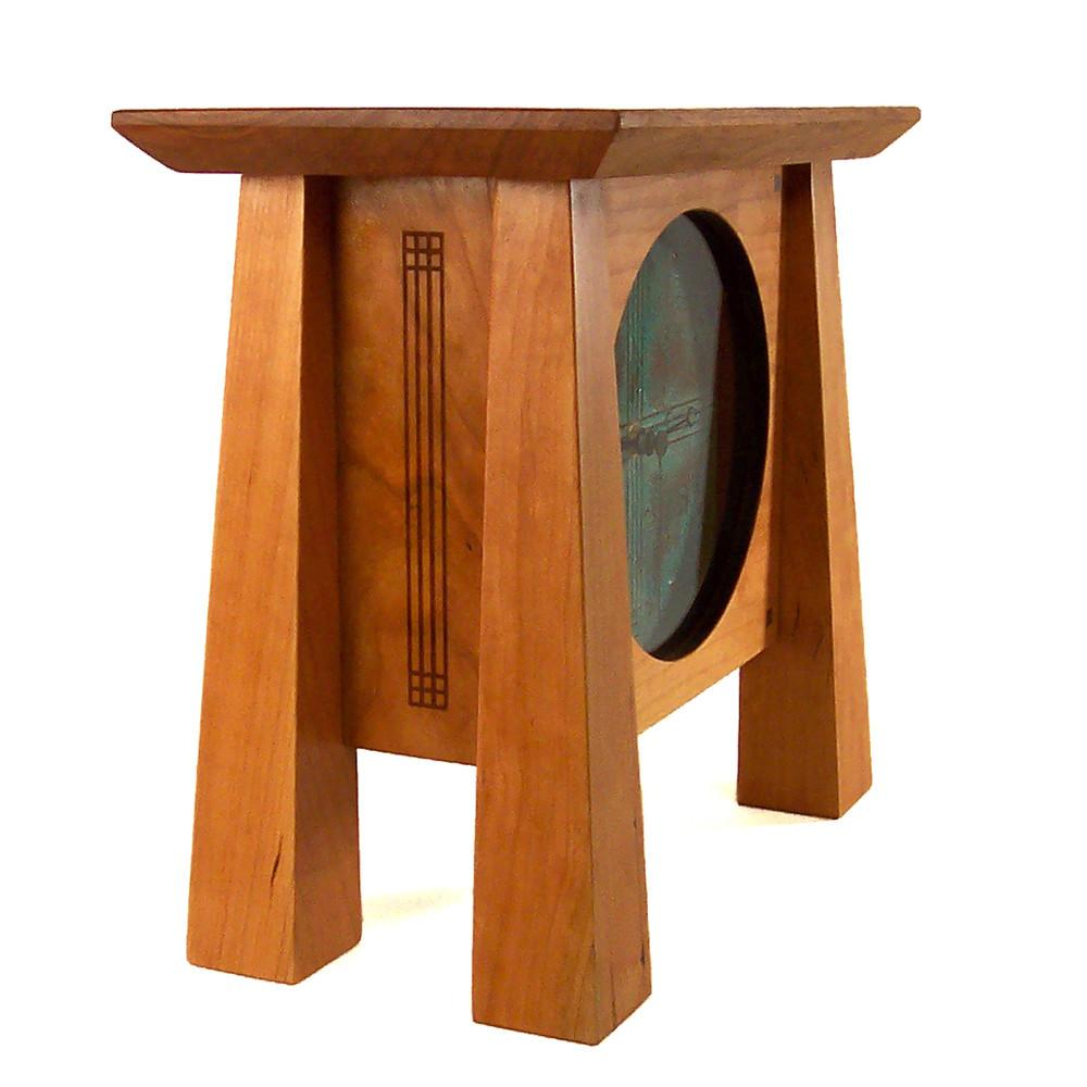 Side view: Cherry wood mantel clock with four tapered legs, patina copper face and pendulum.