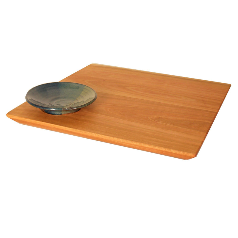 Square cherry wood serving board with green and blue pottery dipping bowl in corner.