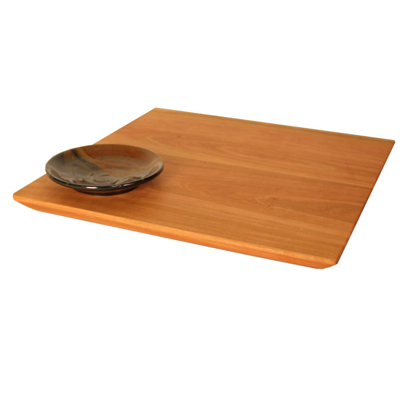 Square cherry wood serving board with black and red pottery dipping bowl in corner.