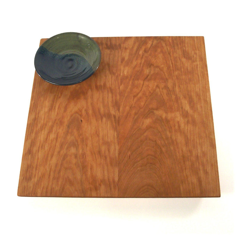 Top view: square cherry wood serving board with green and blue pottery dipping bowl in corner.