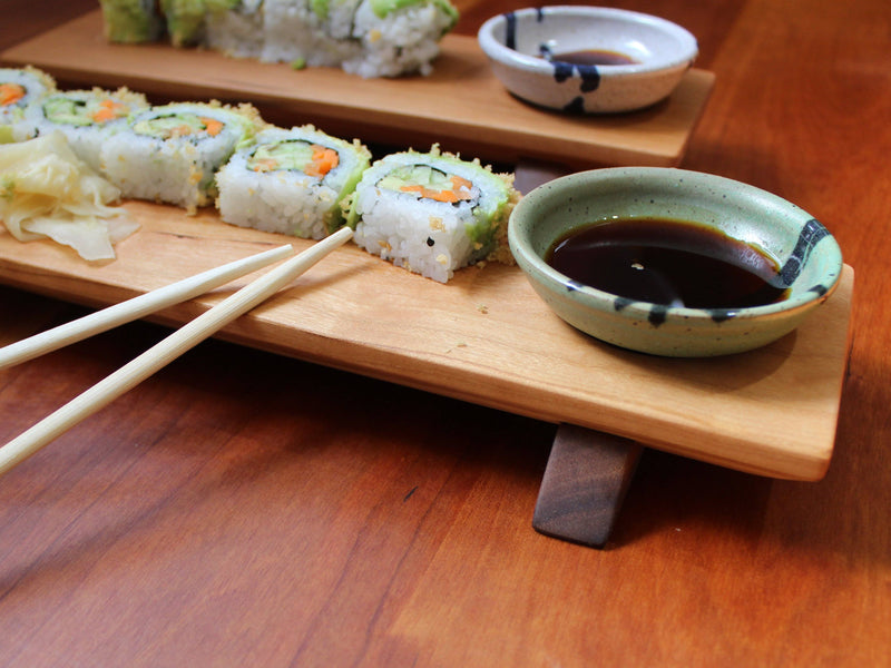 Close-up of sushi board and bowl with fresh sushi, soy sauce in white and blue bowl, and chopsticks.