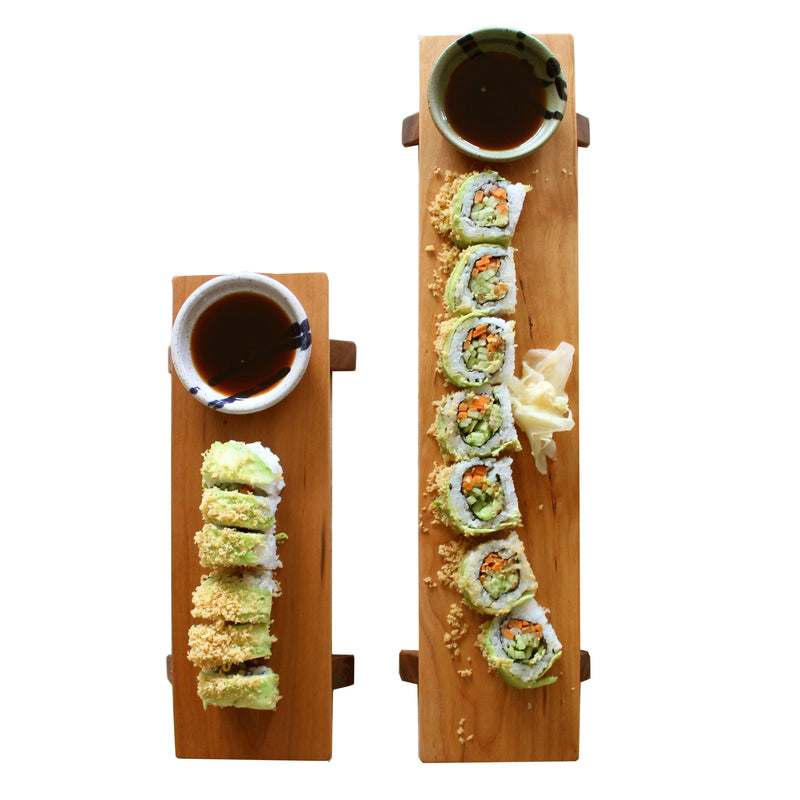 One short and one long cherry wood sushi boards and soy sauce bowls. Sushi & sauce pictured.