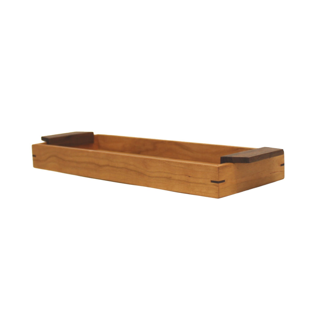 "Angle view: narrow rectangular cherry wood tray with 1.75"" sides and walnut handles on both ends."
