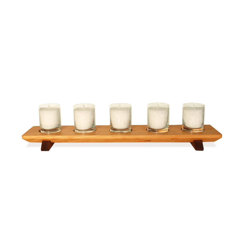 Cherry wood 5-votive holder with walnut wood feet. 5 white textured wax votive candles.