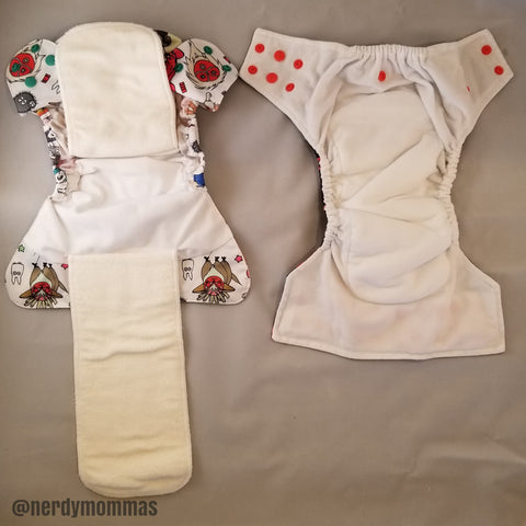 "flat lay photo of two ""All-in-one"" diapers. (left) Flap AIO (Right) sewn-in insert AIO"