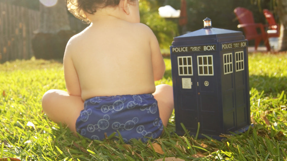 Baby wearing a cloth diaper decorated with the circular gallifreyian for