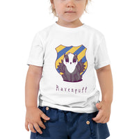black and white badger with wings sitting in front of an emblem seal of yellow and blue stripes shown on a white short sleeve toddler sized t-shirt