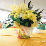 Yellow and white chrysanthemums or mums with assorted paper and sinamay wrappers