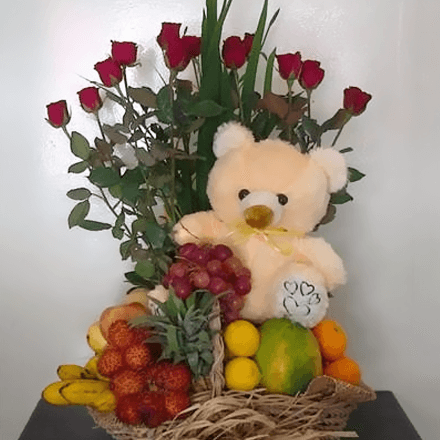 Basket of fruit with a twelve red roses and bear